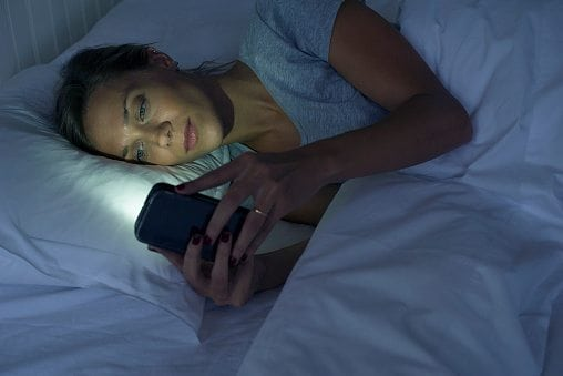 Woman lying in bed using smartphone