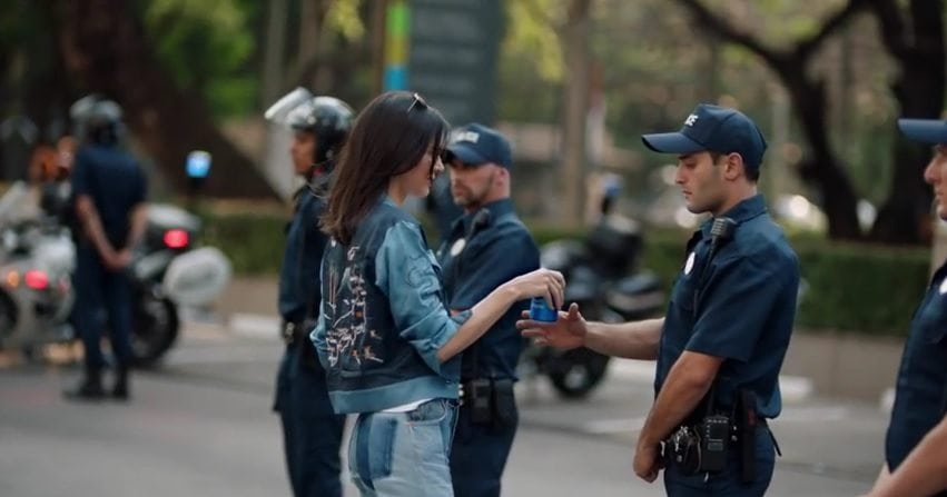Kendall Jenner offering Pepsi to a police officer